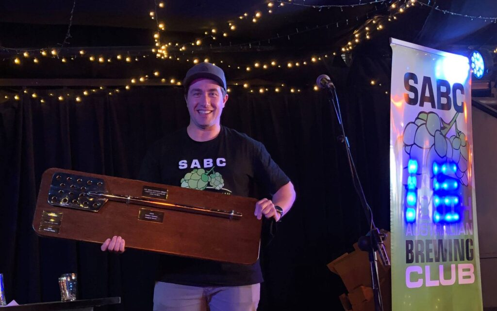 Brendan in SABC t-shirt holds the SABSISA trophy, a silver mash paddle mounted on a wooden board